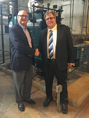 Mark Kelly, President of Able Services, with Bruce Manning, Director of Maintenance at PLB, standing in front of a new boiler at PLB